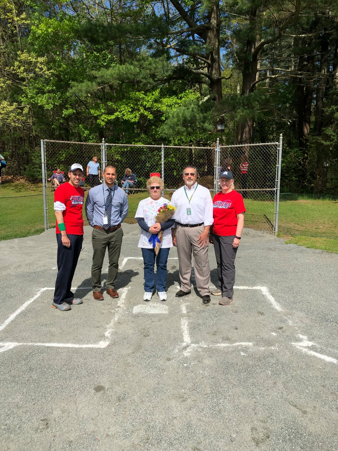 Lady Raiders Coaches, Superintendent Dr. Azar, and Principal Pirraglia at home plate.