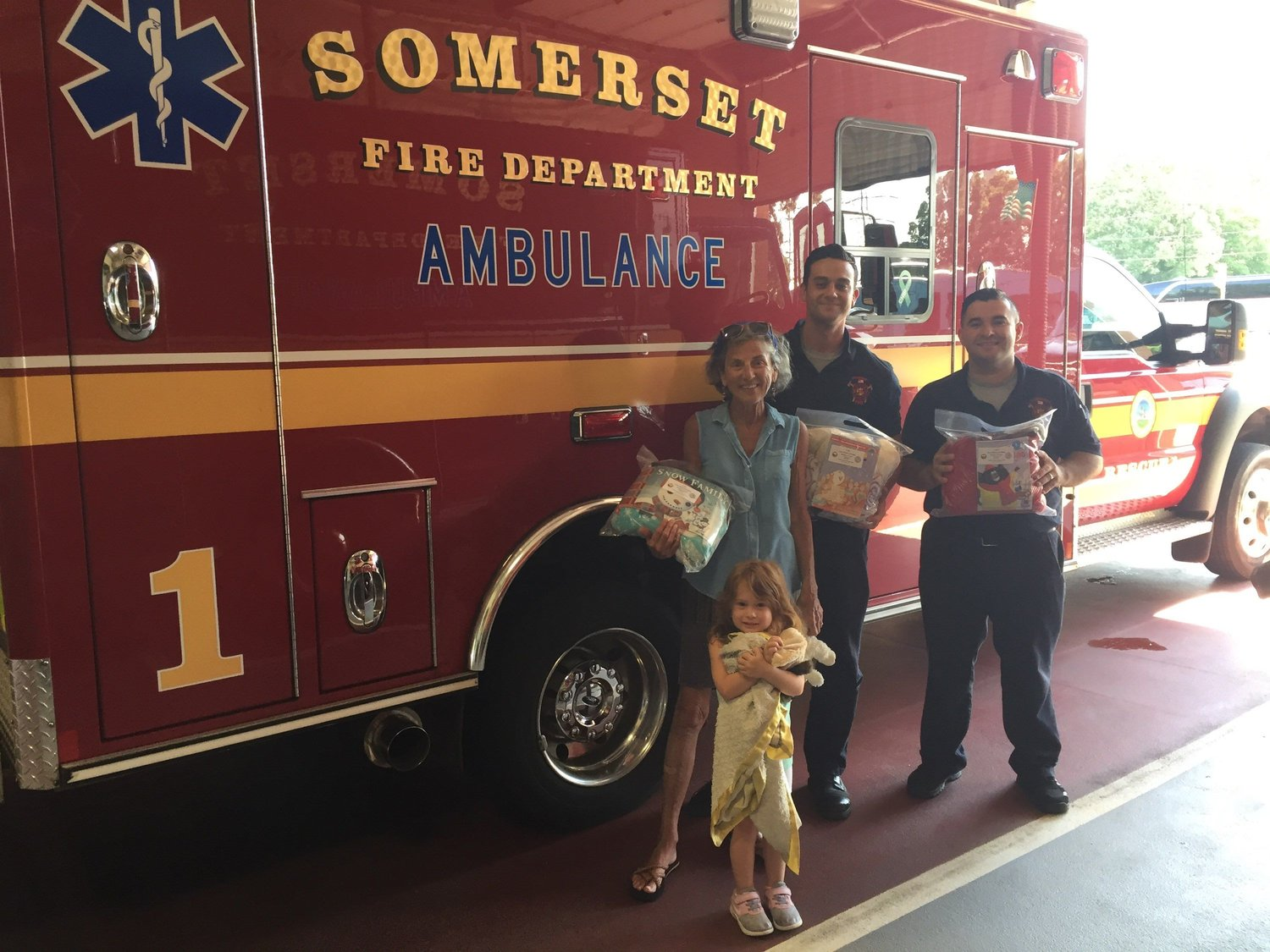 Somerset Fire Department Kathleen Sampson with granddaughter Brooklyn, firefighters Justin Raulino, & Jordan DeMelo