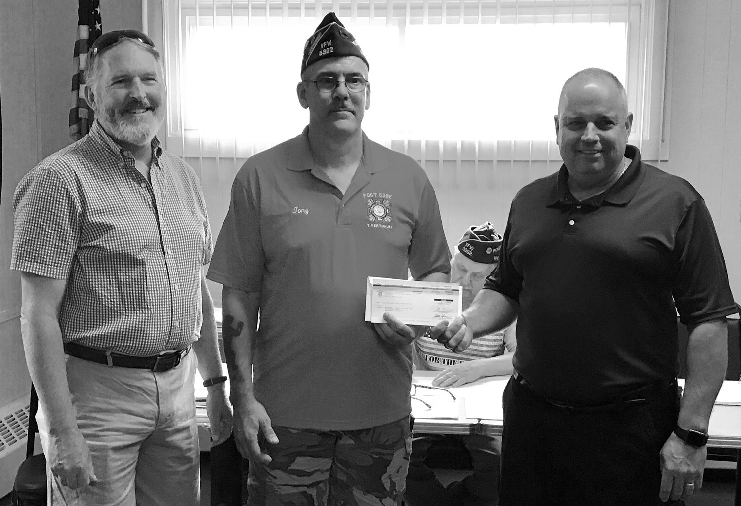 Rep. John G. Edwards, left, and Rep. Dennis M. Canario, right, present a legislative grant check to Tony Lacerda, commander of Post 5392, Veterans of Foreign Wars in Tiverton.