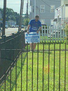 Mr. Orrall, 7th grade English Teacher placing a sign on the lawn of a future Wildcat at Martin Middle School.