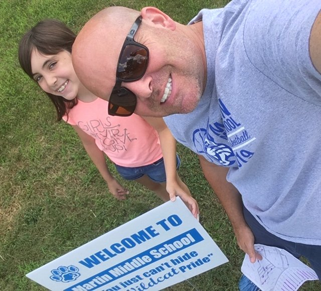Mr. Hunt, Grade 6 Social Studies with his daughter delivering signs.