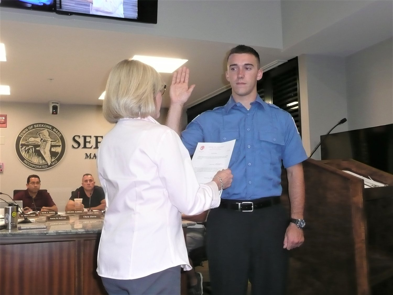 Michael Gould is sworn in as a third class firefighter/paramedic by town clerk Florice Craig at Wednesday's selectmen meeting.