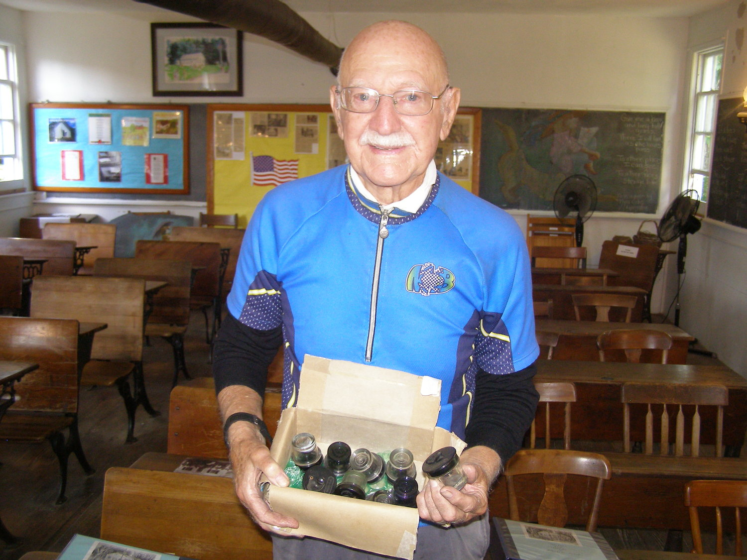 Vincent Luti displaying a box of inkwells he donated to the school.
