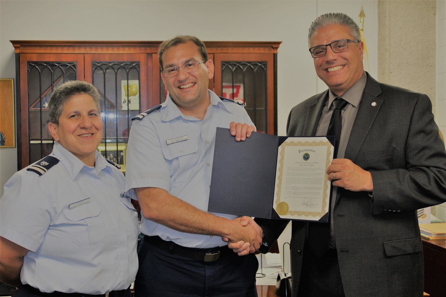 Mayor Bob DaSilva presents a proclamation from the City of East Providence to (L to R):Vice Flotilla Commander Patricia Tarro and Flotilla Commander Chad Cavanaugh.