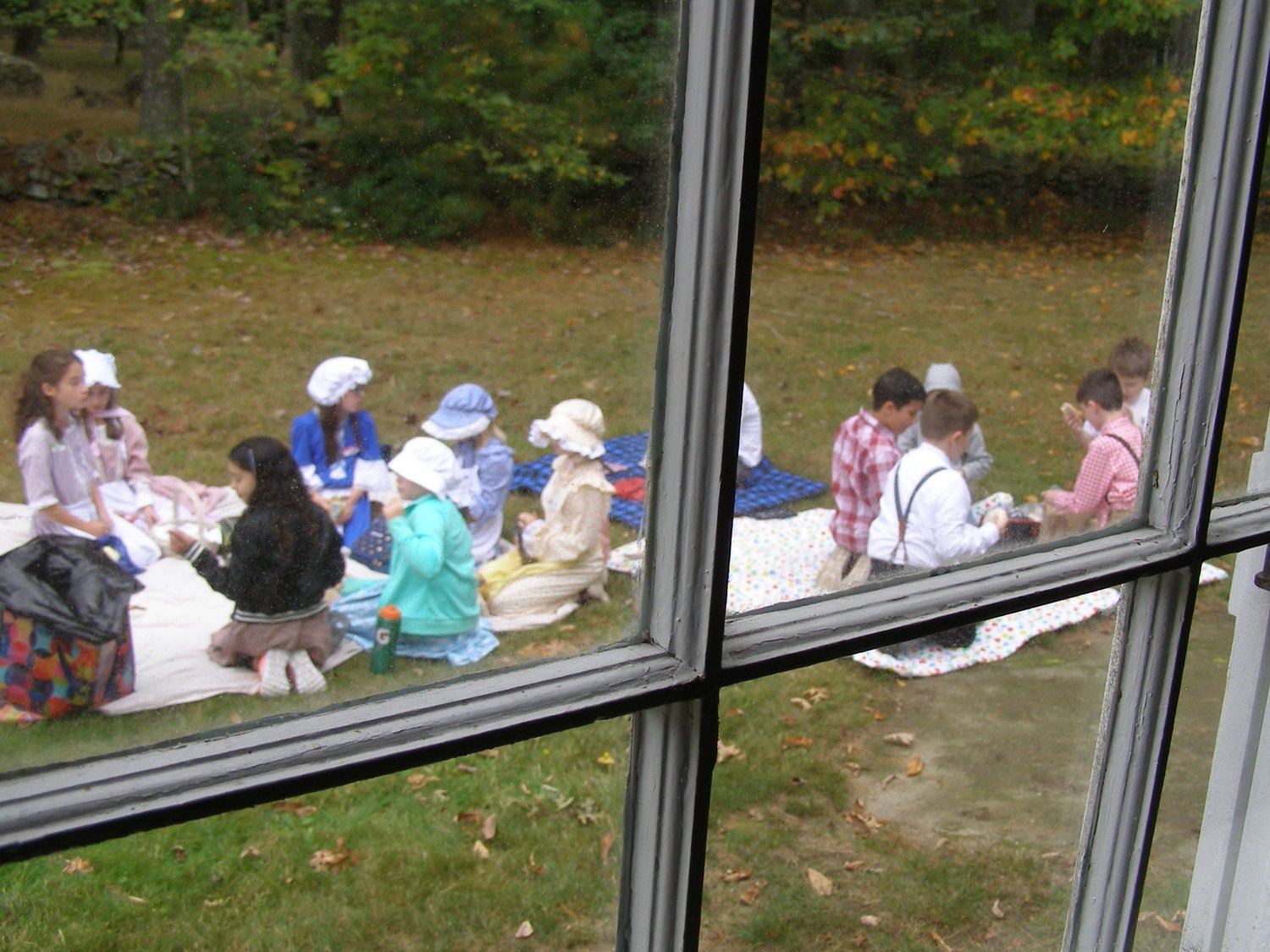 "Children eating lunch outside before playing ""old fashioned"" games for recess."