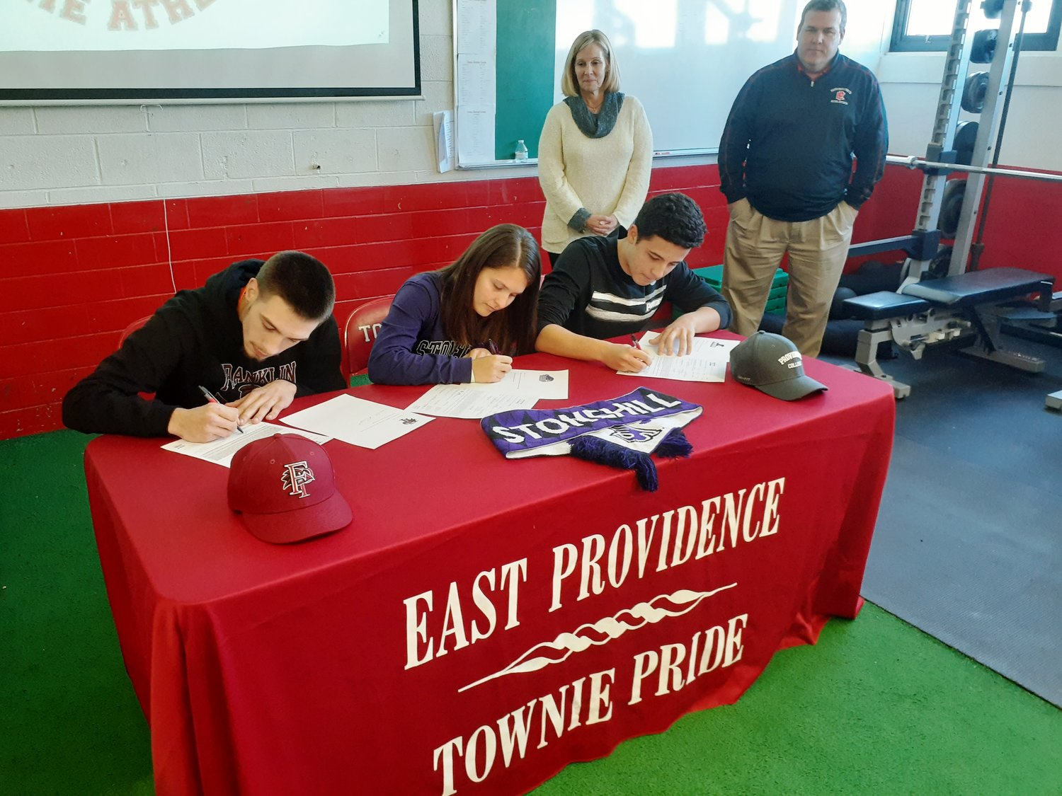 L-R Cole Poissant, Mia Jackson and Yanis Benaduda sign college letters of intent today at EPHS