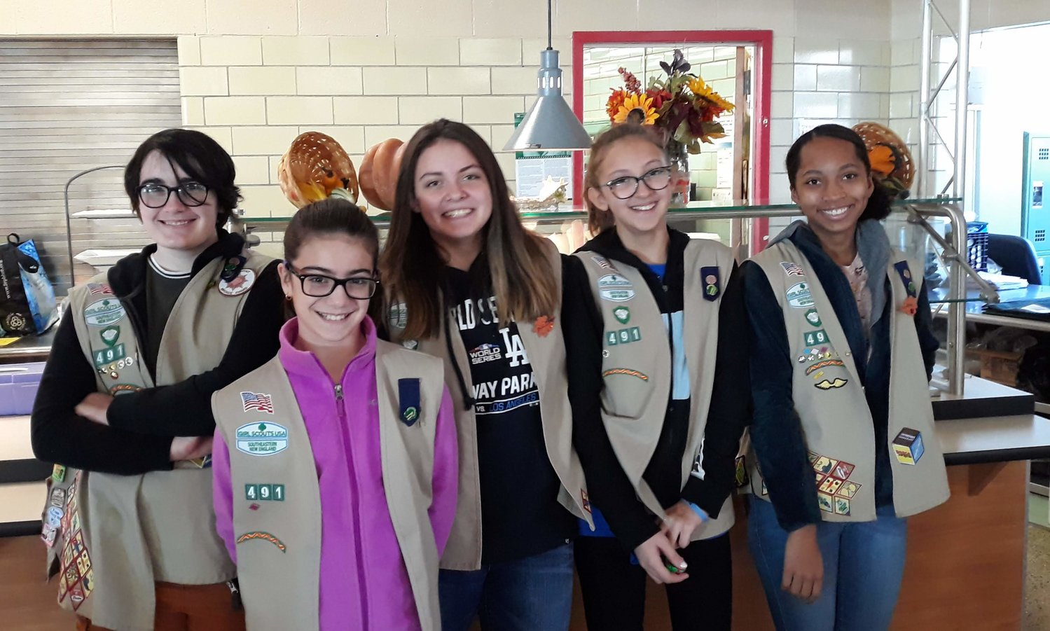 Members of East Providence Girl Scout Troop 491 (from left to right) Lily F, Katelyn D, Abby A, Avarie A, and Rylee J. are shown in front of the cafeteria counter of the East Providence High School where they served food to people who attended the Holiday Craft Fair .