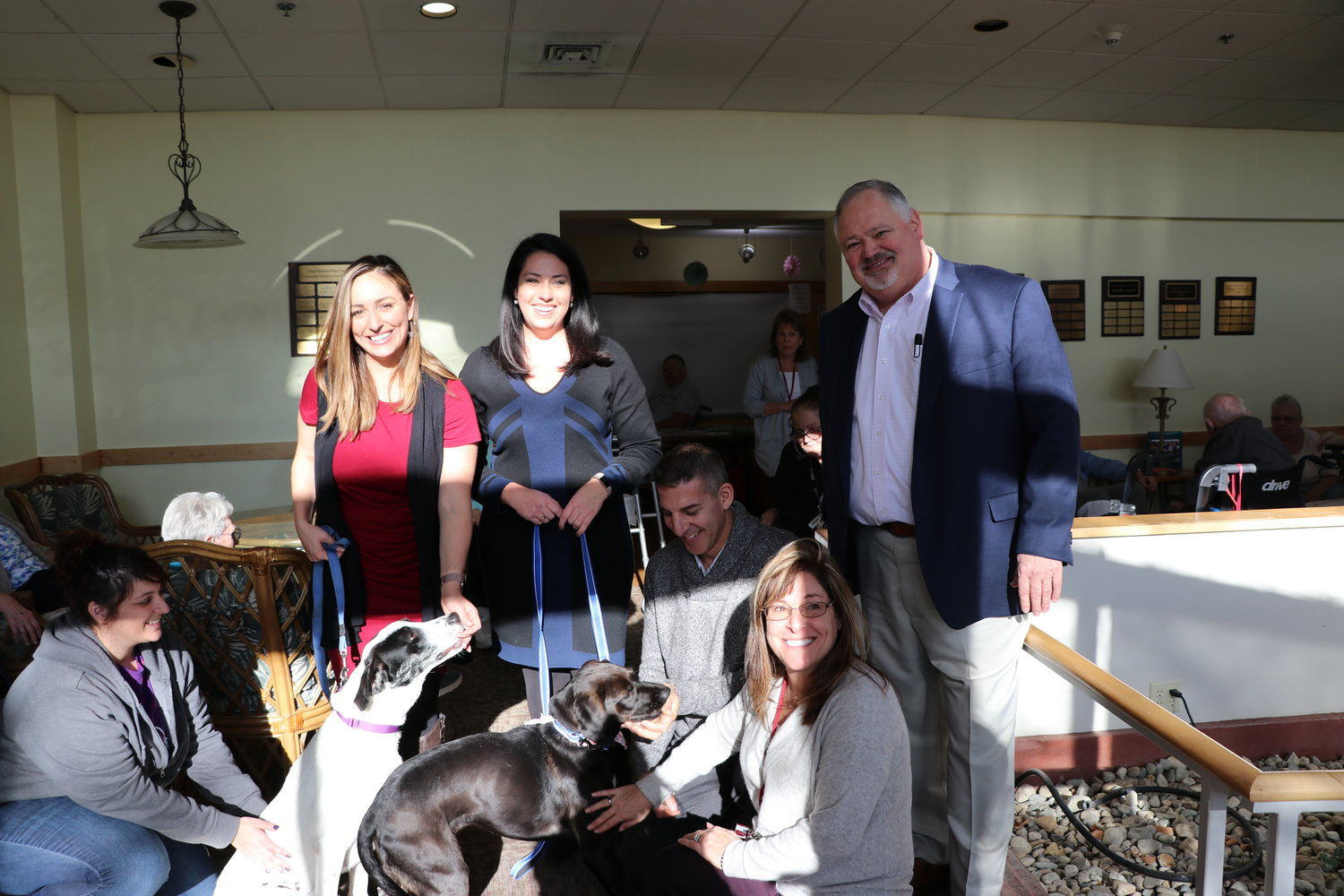 (Bottom row from left) RISPCA Volunteer Coordinator Samantha Nieva; RISPCA dog Magnolia; RISPCA dog Petunia; RISPCA President/General Agent Joe Warzycha, Jr.; Aldersbridge Communities Director of Development, Public Affairs & Philanthropy Elise Strom; (Top row from left) ABC 6 News Anchor Alana Cerrone; ABC 6 Meteorologist Chelsea Priest; Aldersbridge Communities Chief Executive Officer Richard Gamache. All pictured while ABC 6 on-air talent were visiting residents of Aldersbridge Communities in East Providence.