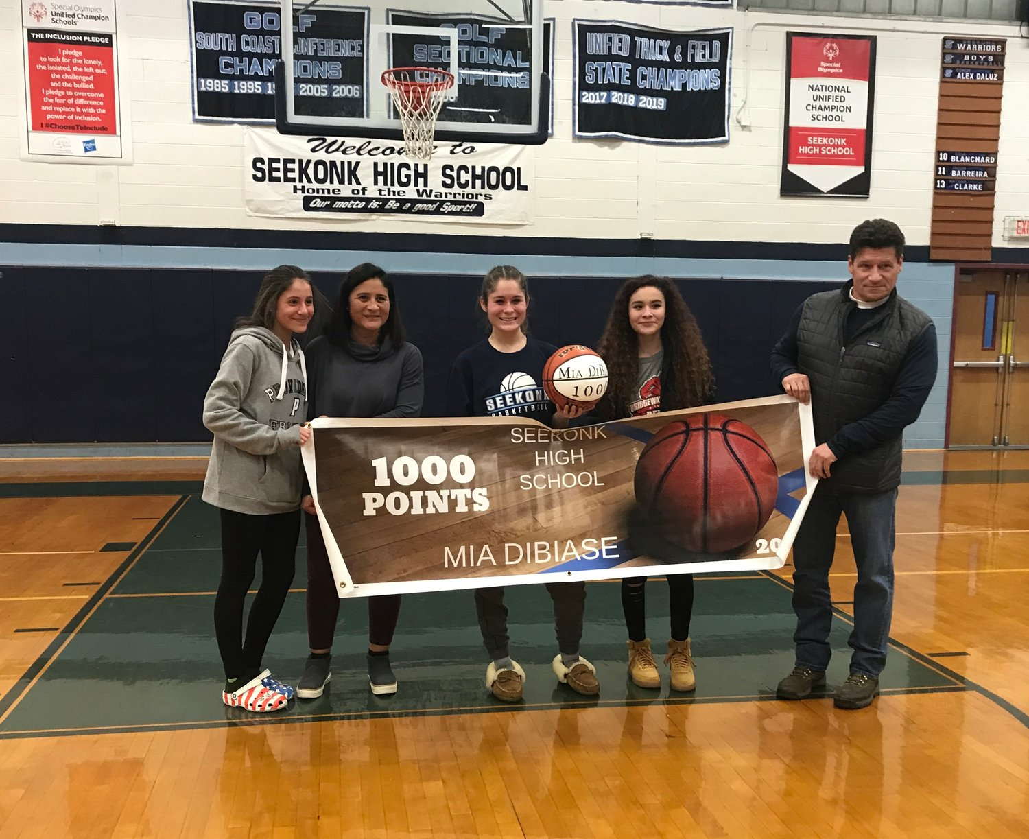 Seekonk senior Mia DiBiase celebrates with her family after the game in which she scored her 1,000th point.