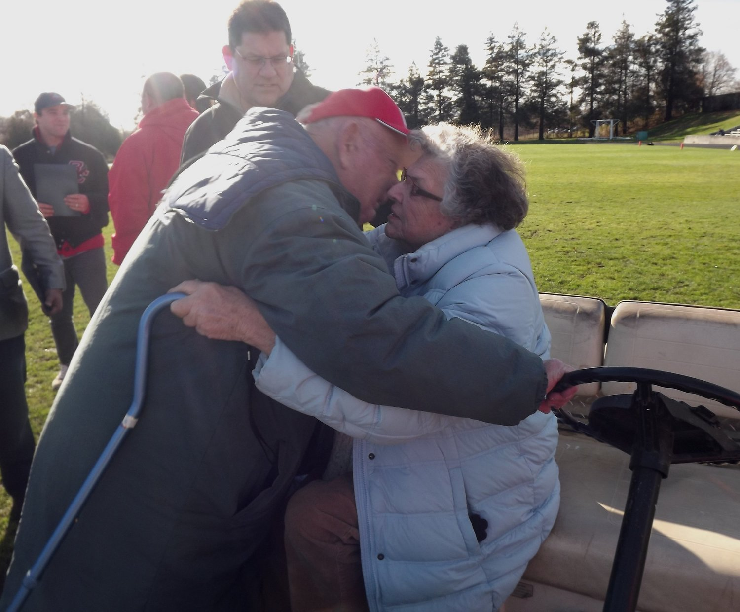 As the sun shone brightly down on Pierce Stadium, Bill Stringfellow tells whispers I love you, to wife Sheila. Pierce Stadium honored them Thanksgiving Day 2014.