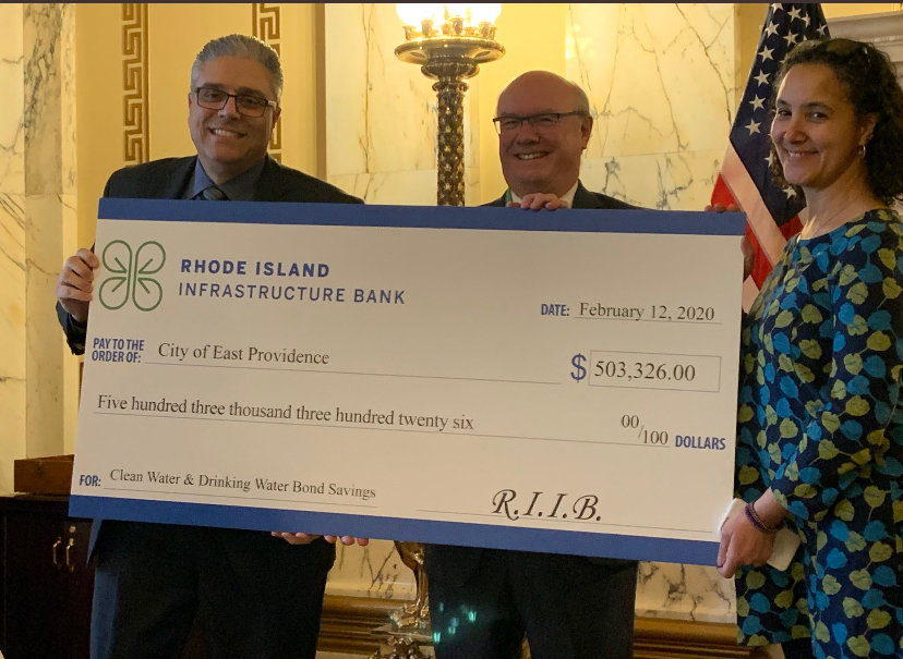 Mayor Bob DaSilva, Jeffrey Diehl (CEO of Rhode Island Infrastructure Bank) and Rep. Liana Cassar hold a refund check from RIIB in the amount of $503,326. The refund will be used to fund future capital projects in East Providence