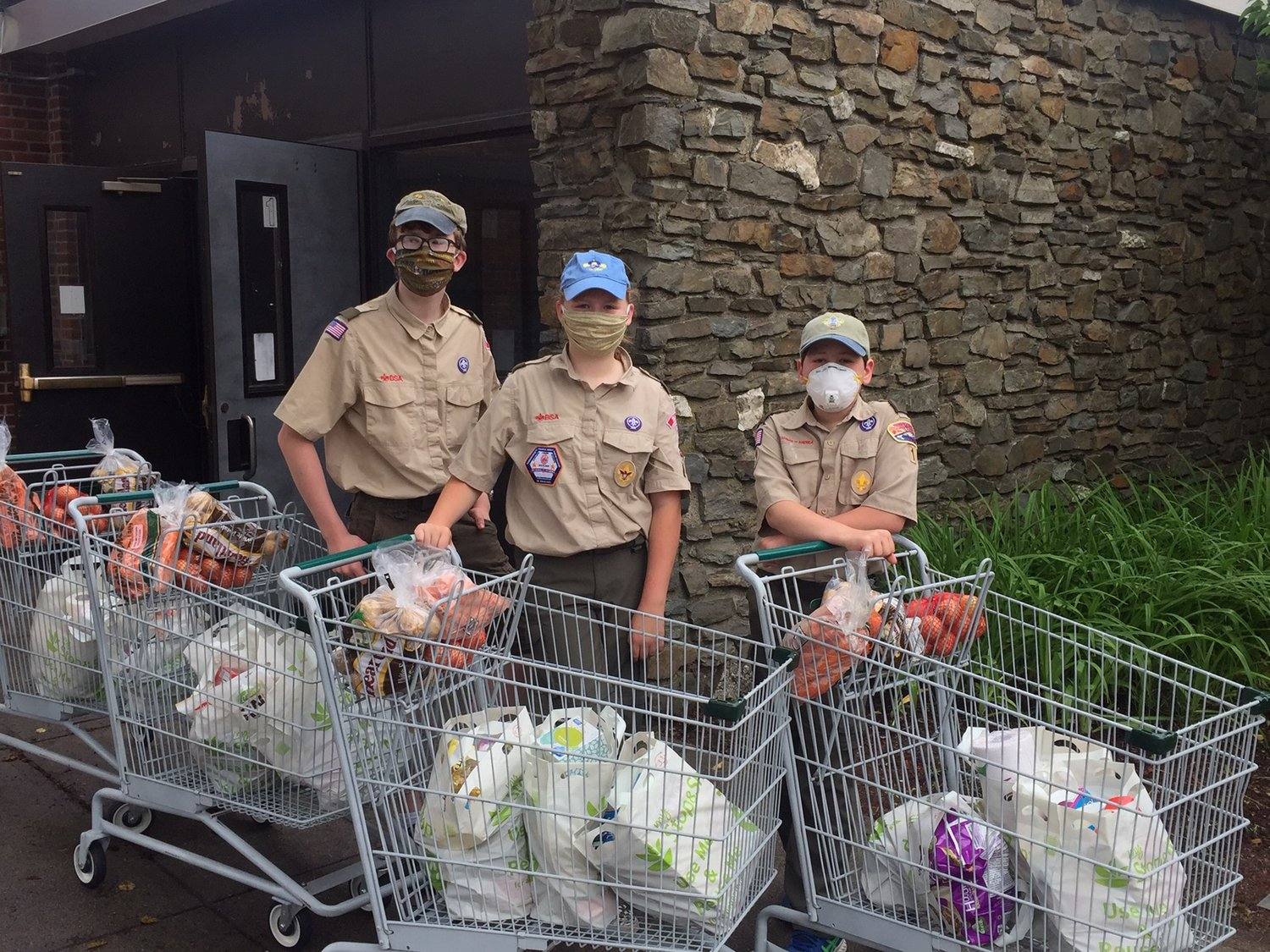 Scouts from BSA Troops 1 & 9 assisting with curbside distribution at Doorways