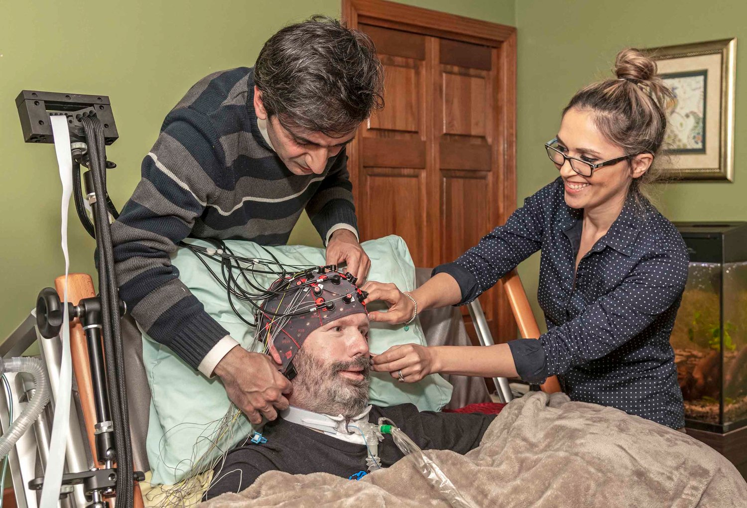URI doctoral student Bahram Borgheai and URI Assistant Professor Yalda Shahriari (right) adjust the cap used to monitor ALS patient Doug Sawyer's brain activity.