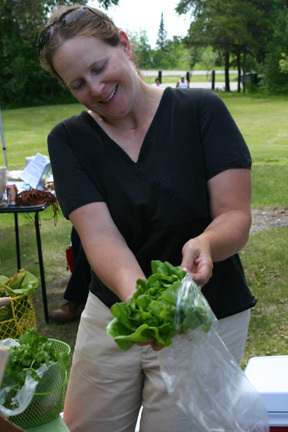 Janna Goerdt, of Embarrass, bags up some lettuce from her farm.
