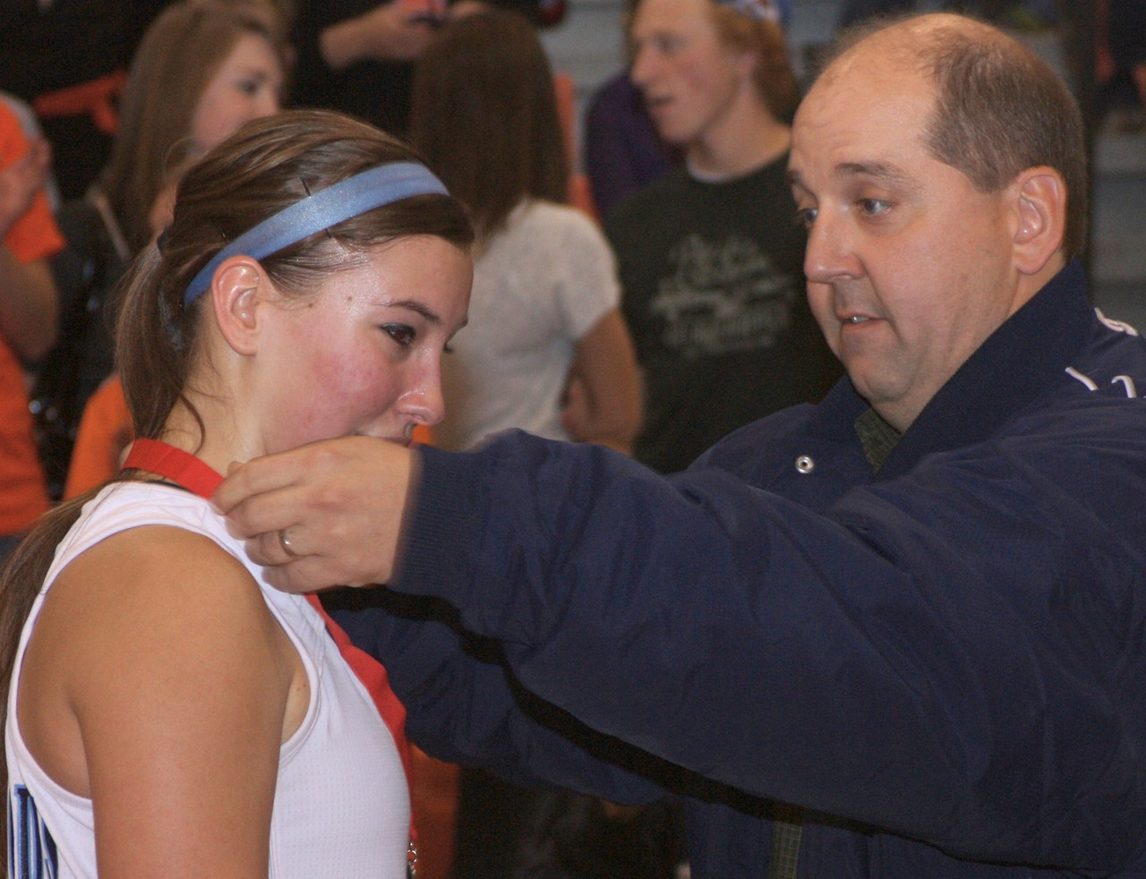 Katie Zallar receives her medal from ISD 2142 co-athletic director John Jirik.
