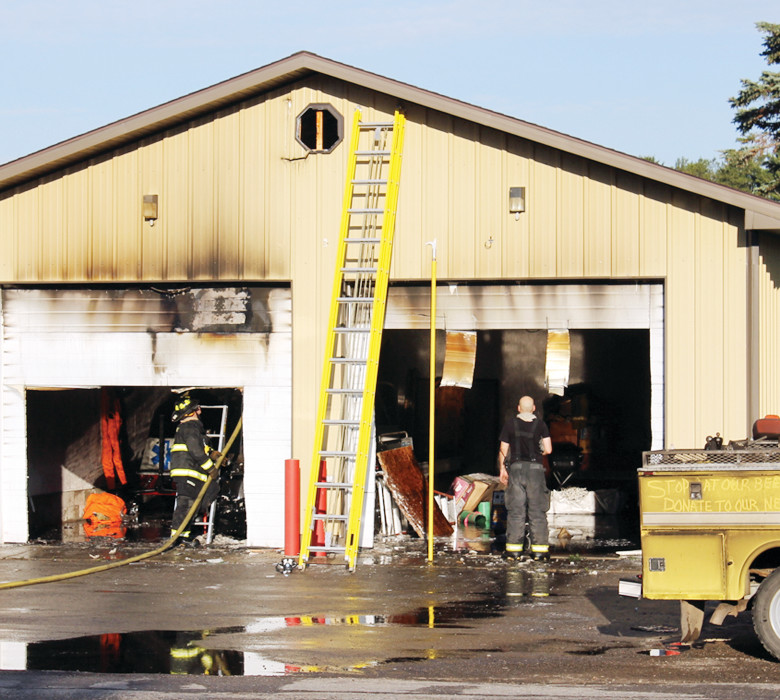 Firefighters in Tower survey the damage to their storage building following an early morning fire on July 4.