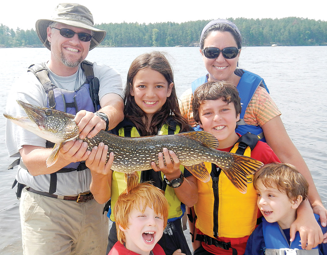 Joseph Goldstein, 13, center, holds a northern pike caught last August in Iron Lake in the Boundary Waters Canoe Area. He