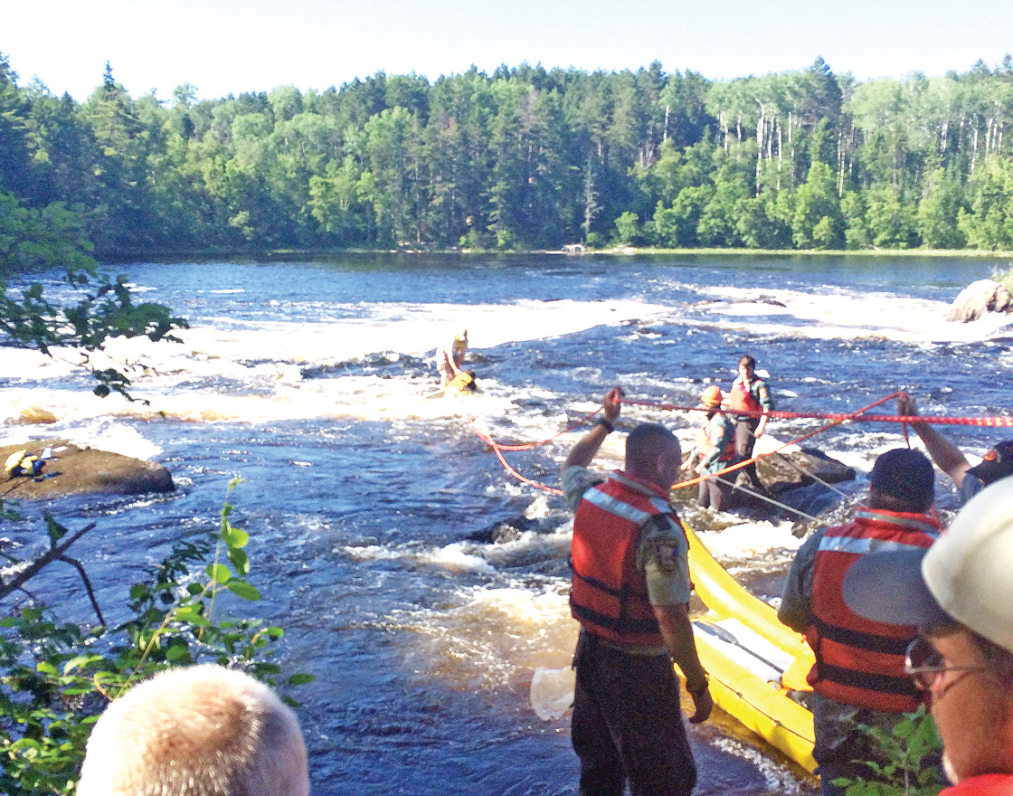 St. Louis County Rescue Squad members work Tuesday to save a canoeist at Cable Rapids on the Basswood River in the Boundary Waters Canoe Area Wilderness.