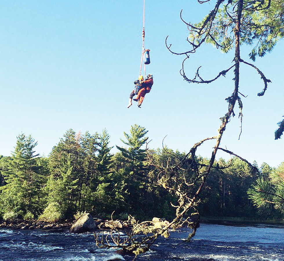 An injured canoist and rescue personnel are hoisted up to a Minnesota State Patrol 