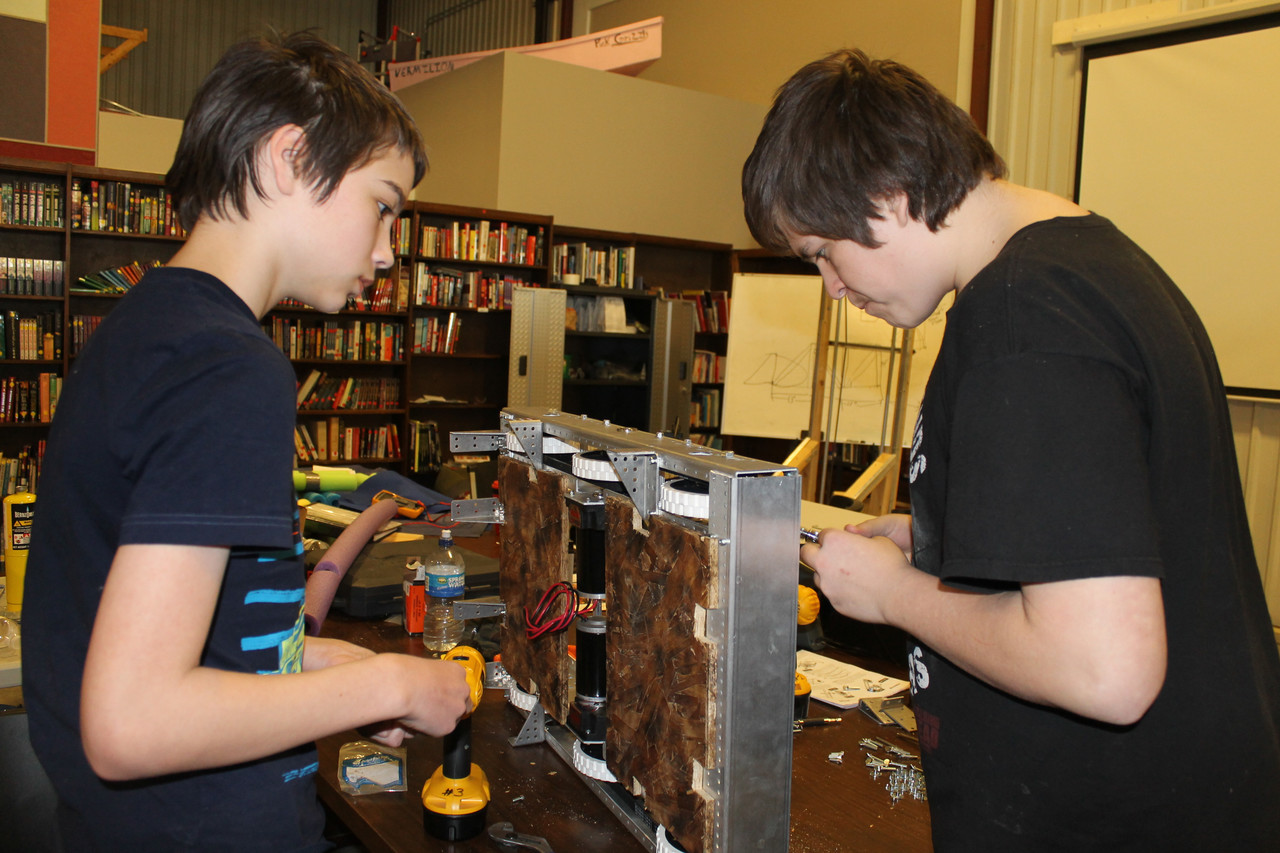 Alex Dorman (left) and Daniel Kuriatnyk (right) start wiring the motors that will power the robot's wheels.