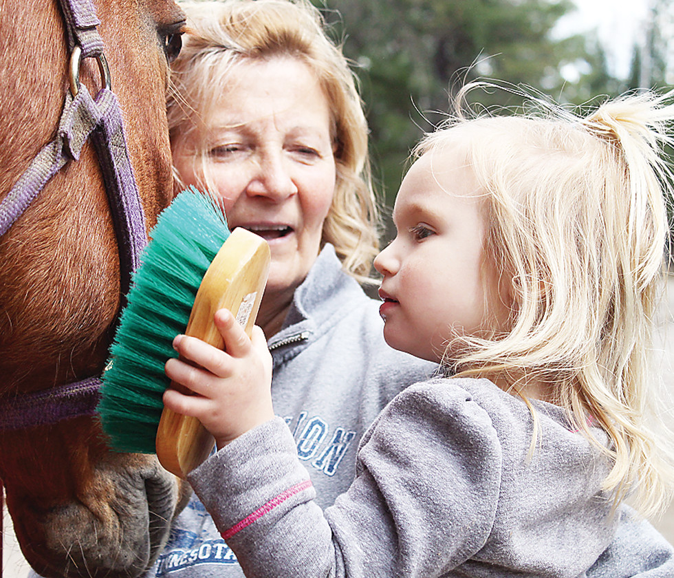 Elyse Jola, gets up close and personal to brush a horse with her grandmother, Pam Myre, one of the organizers of the hobo ride.