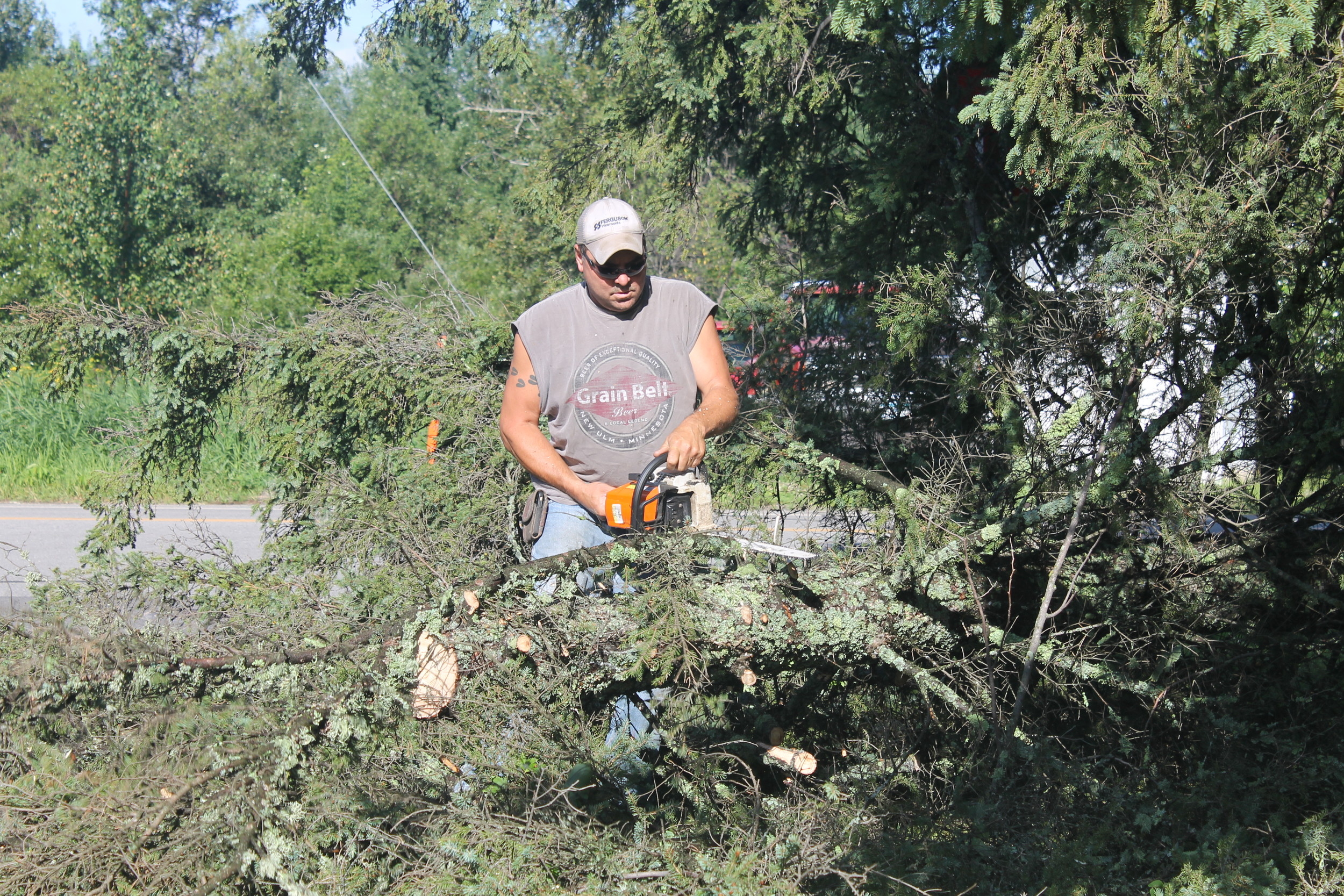 Tower maintenance worker Dave Bjorgo cuts up a tree that blew down on North Second St.