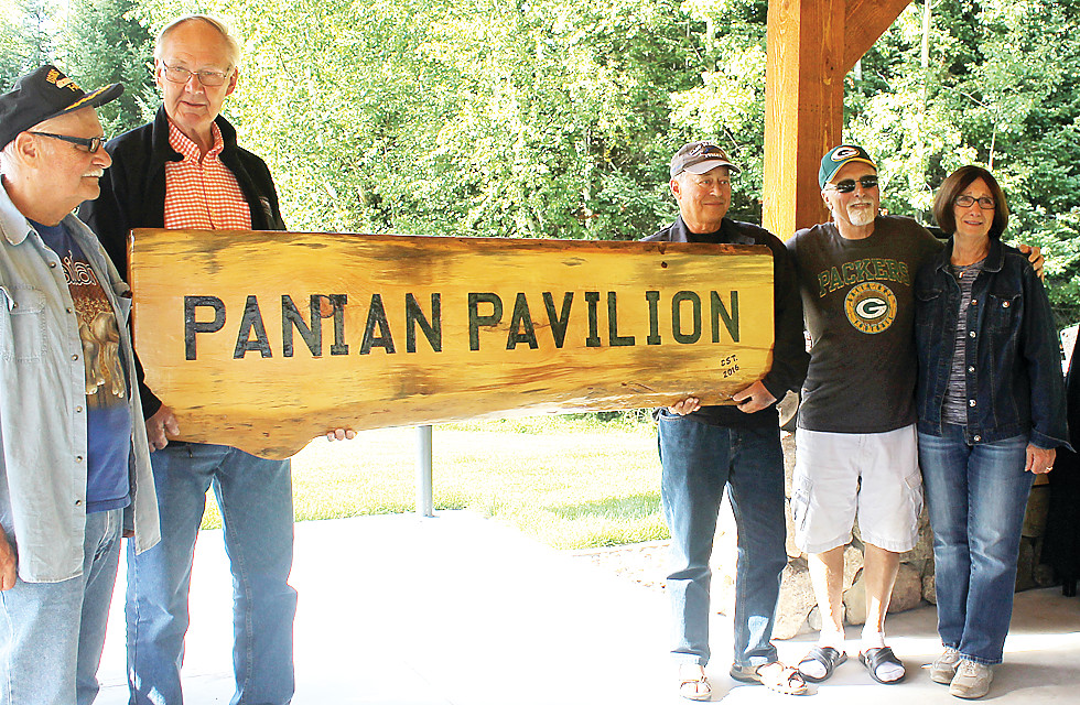 Friends and family of Dean Panian hold up the new sign 