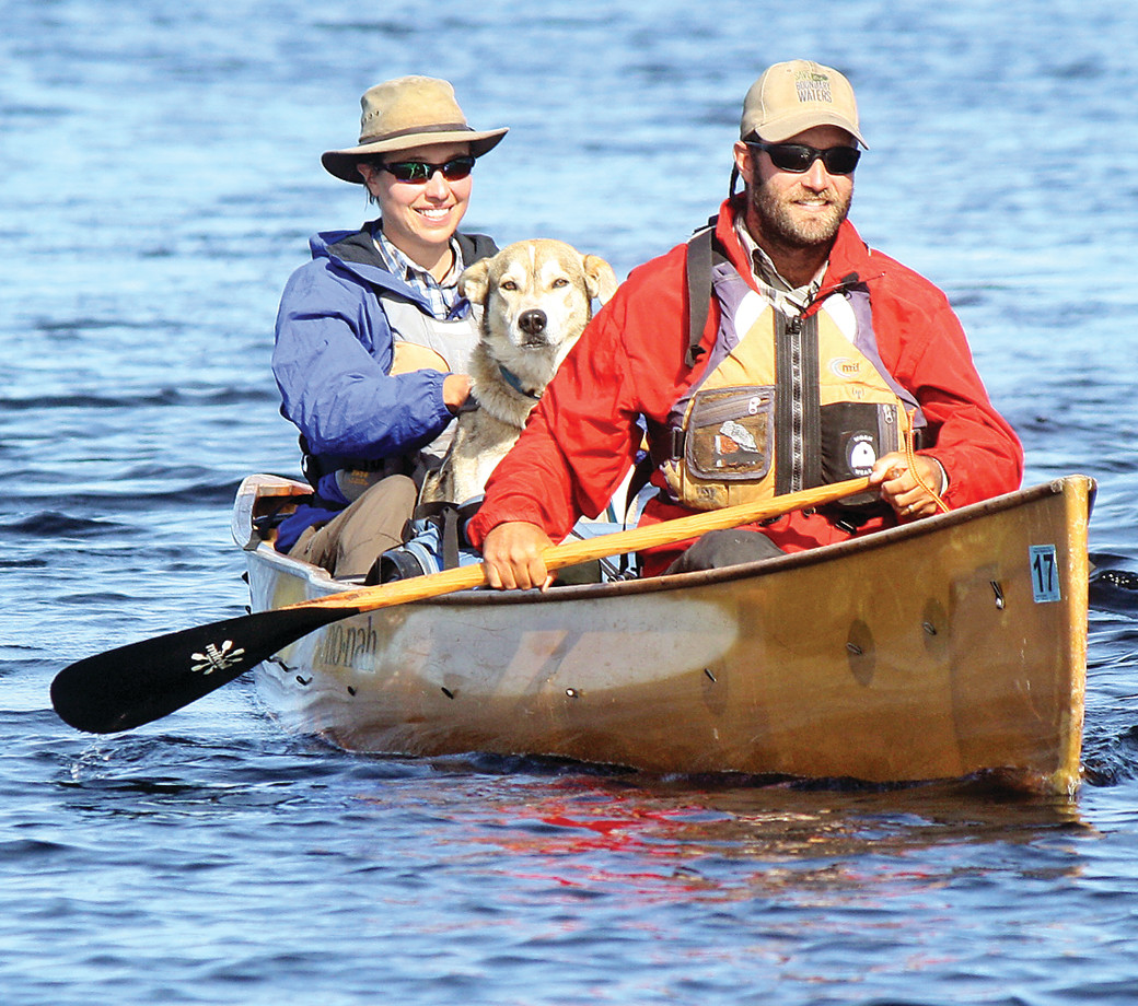 "David and Amy Freeman, along with their adopted sled dog, ""Tank,"" paddle to the shore of River Point Resort and Outfitters on Birch Lake last Friday, 365 days after they left the same point to spend a year in the Boundary Waters Canoe Area Wilderness in an effort to draw attention to the risks of a proposed sulfide mining project adjacent to the wilderness."