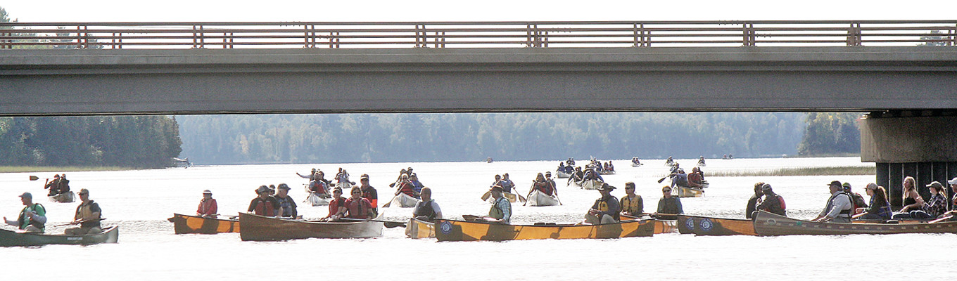 A flotilla of paddlers in 60-plus canoes and kayaks waited to greet David and Amy Freeman last Friday at the Highway 1 bridge on Birch Lake.