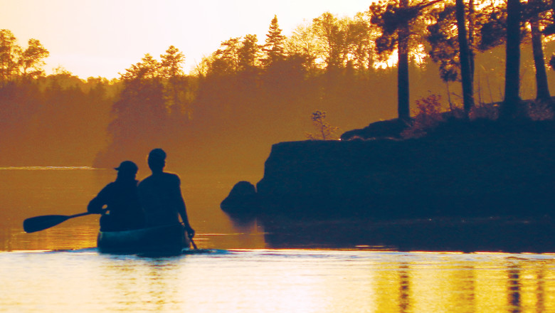 Canoeists paddle into the sunset on Farm Lake in the Boundary Waters Canoe Area Wilderness.