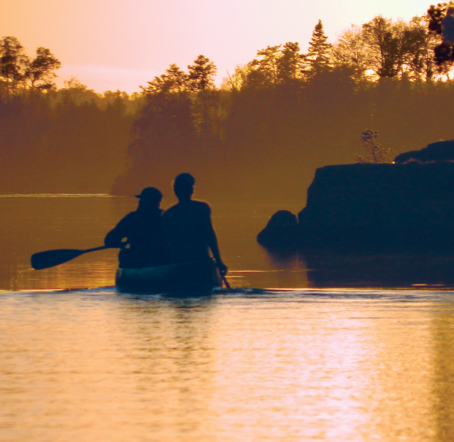 Canoeists paddle into the sunset on Farm Lake, near Ely.