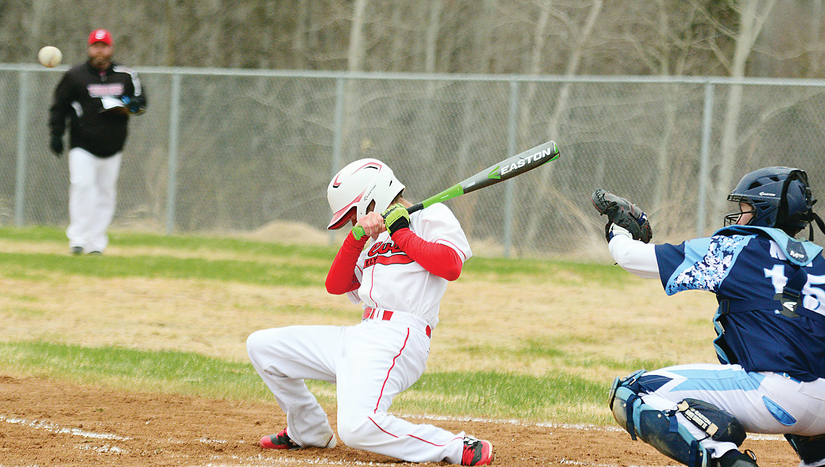 An Ely player ducks away just ahead of an inside pitch.