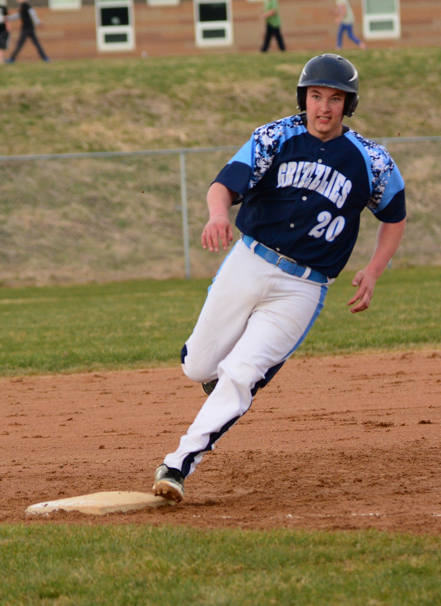 North Woods senior Colton Arvila picks up the sign as he rounds third base and scores in the Grizzlies' 5-4 home win over Mesabi East on Thursday.