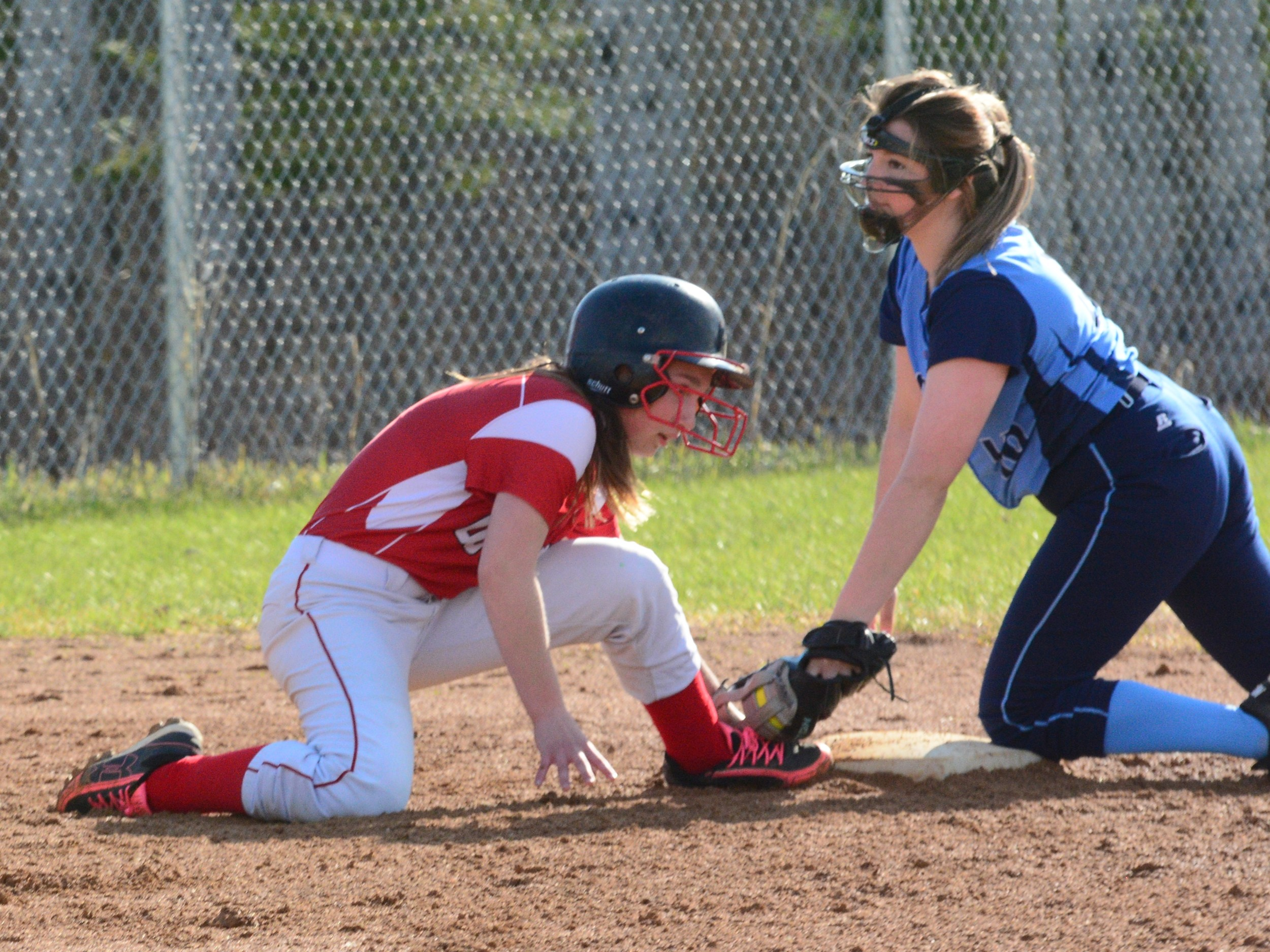 Ely's Charly Flom, left, dives back into third base as North Woods' Maddy Serna drops down a tag during Thursday's showdown.
