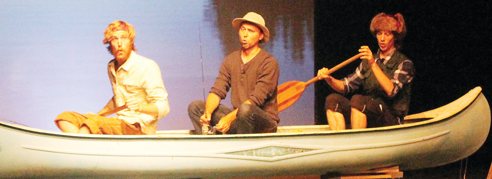 "Cast members sing ""The Walleye Song"" while paddling a canoe across the stage. Pictured are Ethan Shiffman, Luke Morgan, and Caleb 