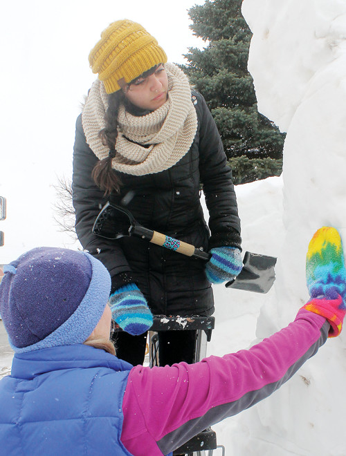 Emma Kari, the Ely high school art student who designed the 2018 Winter Festival pin gets a snow sculpting lesson from Nancy Schiebe at the Front Porch Coffee and Tea Co.
