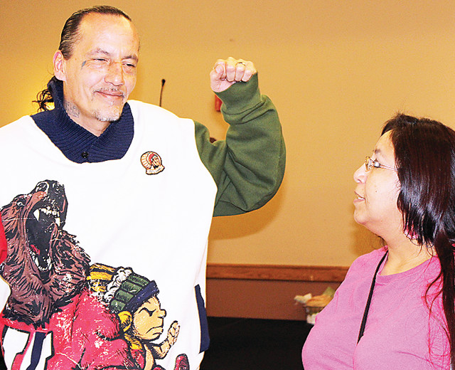 James Cross, founder of Natives Against Heroin, talks with an opioid forum participant last week at Fortune Bay.