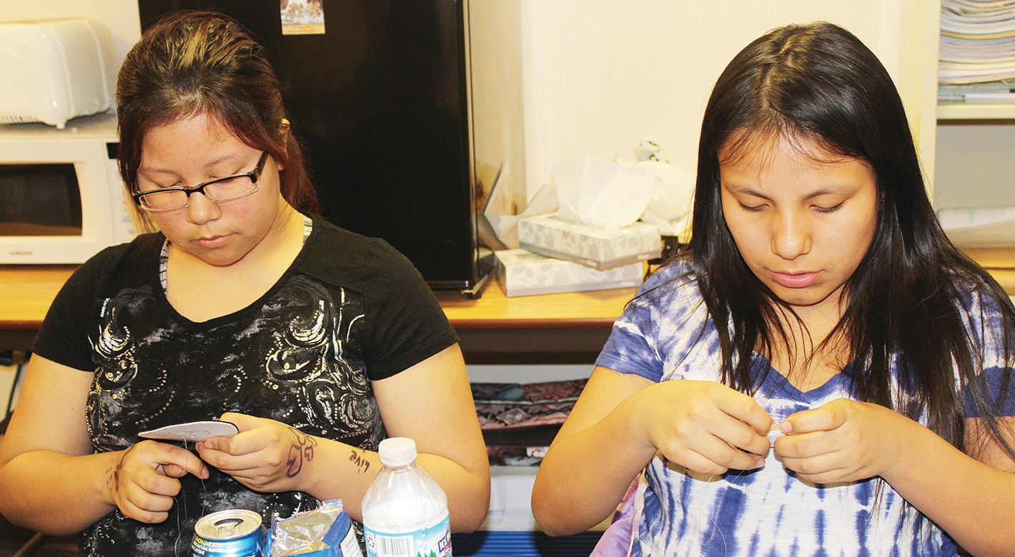 Anissa Pete and Mahlia Schuster concentrate on their beading projects.