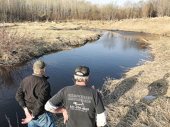 Julian Brzoznowski and Jerry Christenson, the new owner of the Brzoznowskis family farm, watch just-stocked brown trout surfacing to feed in Kinmount Creek.