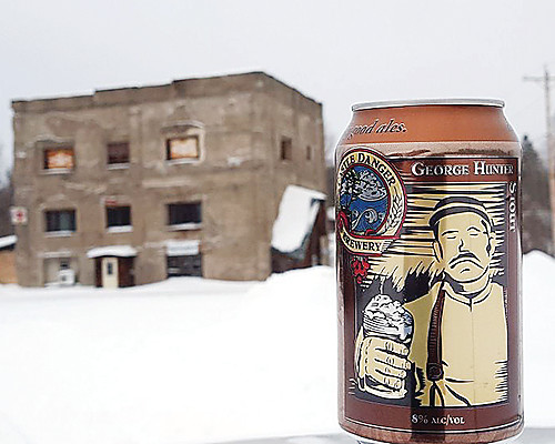 A north woods connection: A can of George Hunter Stout with the remains of the former Iron Range Brewing Co. in the backgrouond. The beer, produced by the Castle Danger Brewing Company, is named after Tower's original brewmaster.