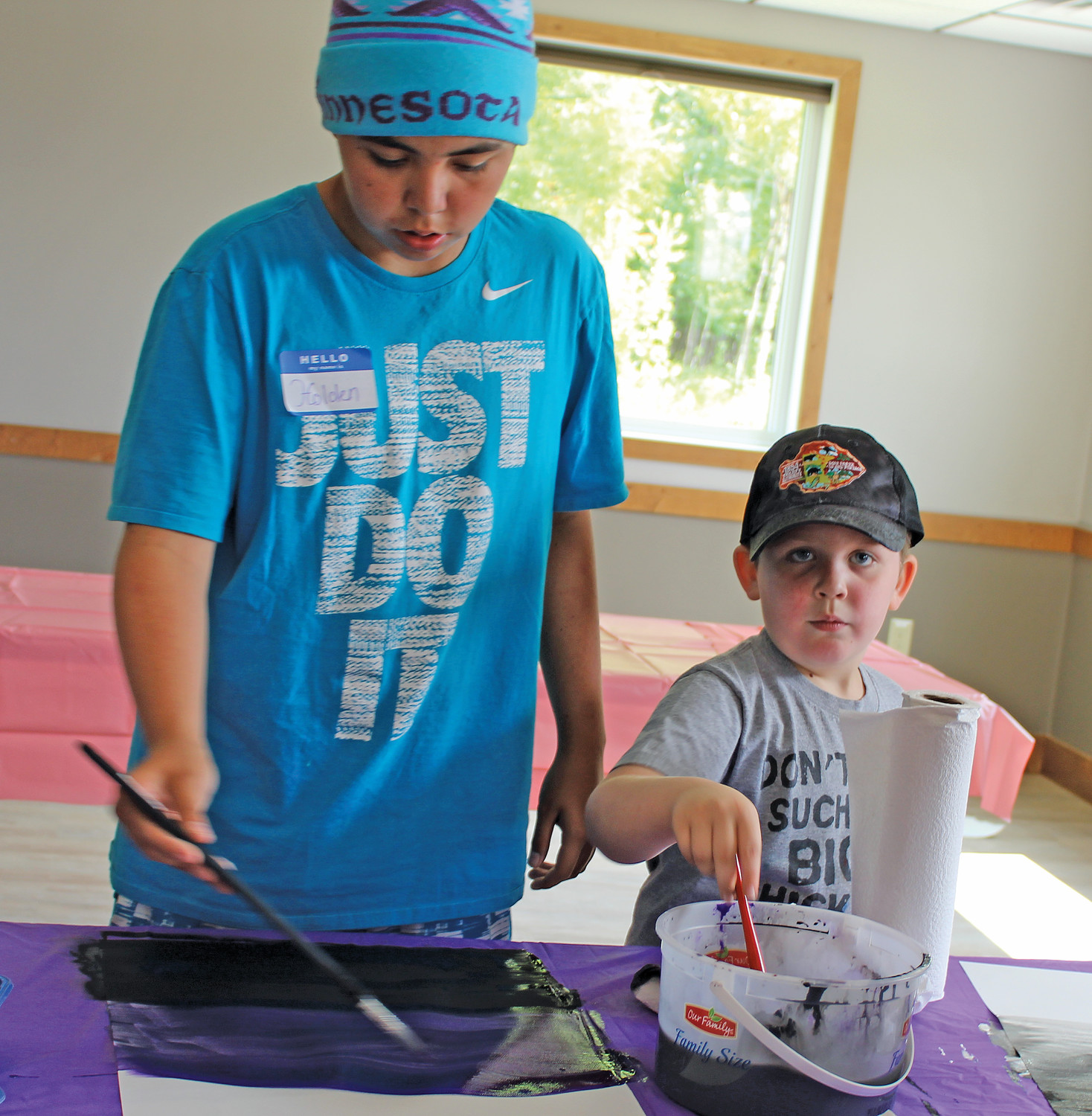 Holden Benner (left) and Gabryl Bucholtz practice painting before lending their skills to painting wings.