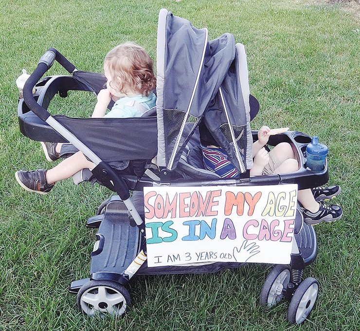 "A child's stroller displays a sign reading ""Someone my age is in a cage,"" at the Lights for Liberty event. submitted photos"