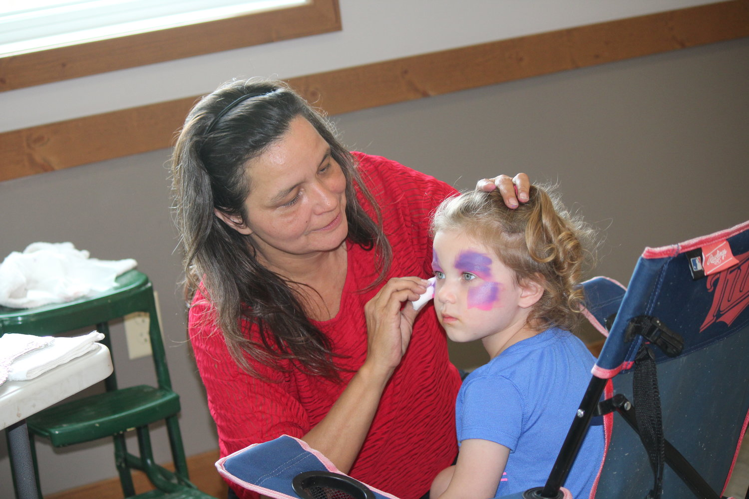 Tracey Robinson paints the face of Maren Foss, 2, of Cook inside the community center.