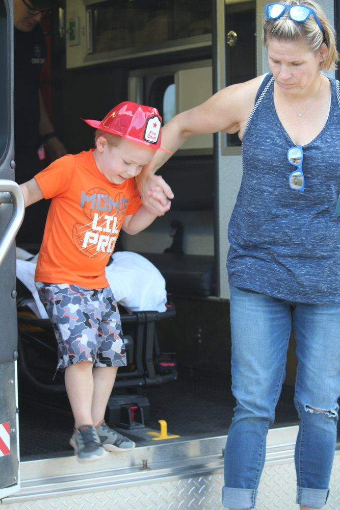 Caroline Roesch helps son Sullivan, 4, of Cook out of the ambulance after he explored the rig.