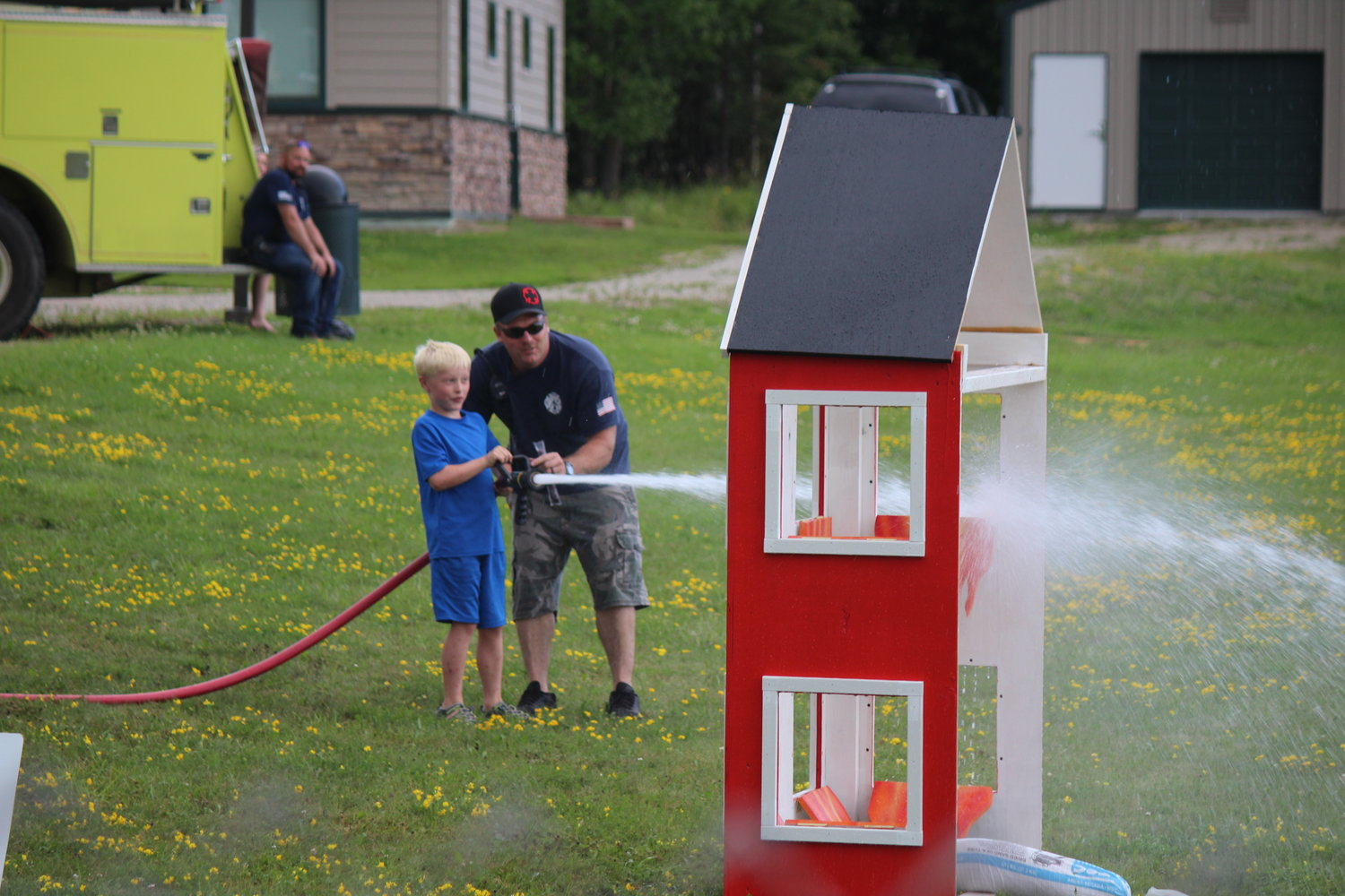 Cook Volunteer Firefighter Jon Rothluetner helps Grant Bixby Meehan, 8, hoist a hefty hose at the mock firehouse.
