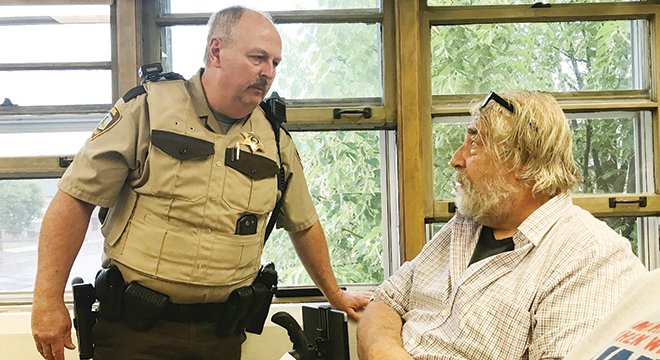 Breitung Township officer Jim Battin ejects Tower News commentator Tony Sikora from the Tower City Council meeting on Monday.