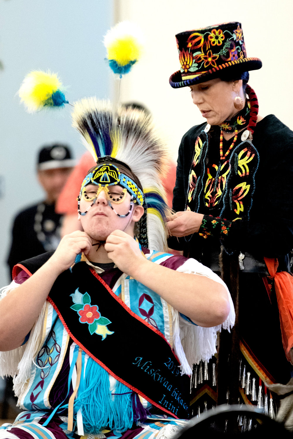 Gretchen Morris makes final adjustments to her son Dillion's outfit prior to Sunday's grand entry at the Bois Forte Midwinter Pow Wow at Nett Lake.