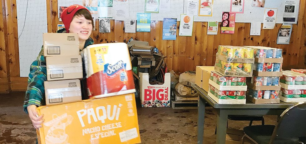 A Vermilion Country School student helps unload the foodbank truck at the Tower Food Shelf. With students now at home, the food shelf needs more volunteers.