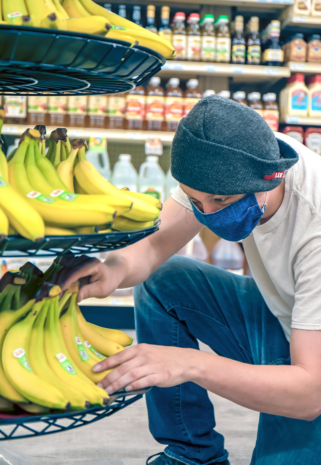 Shortly after the Cook Zup's opened at 7 a.m. on Wednesday, Gage Koskovich puts the finishing touches on a display of bananas.