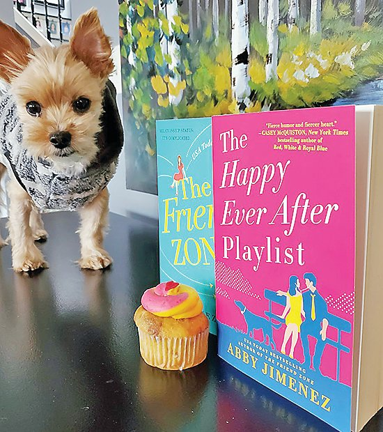 Author Abby Jimenez's dog Stuntman Mike with the cover of her new book and a cupcake.